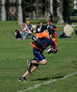 A photo of a lacrosse player in full sprint attack with the ball clearly visible in the pocket of his lacrosse stick. The player is dressed in orange and dark blue surrounded by a field of green turf with spectators looking on from the sidelines.  Lacrosse Team Accommodation lacrosee4