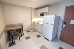 Image of the kitchenette at RCC - Barrie. There\'s a full-size fridge, microwave, counter space with sink, and kitchen table with two chairs.