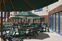 Image of the Back Patio space at RCC - Barrie. There\'s a number of tables and chairs with umbrellas