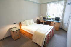 Image of one of  the bedrooms in the suites at RCC - Barrie. Includes a double XL bed, a dresser, desk, chair and Television.