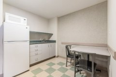 Image of the kitchenette at RCC - Hamilton. There\'s a full-size fridge, microwave, counter space with sink, and kitchen table with two chairs.