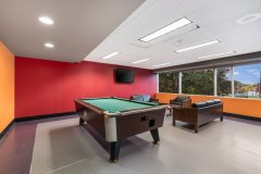 Image of the games room at RCC - Hamilton. There\'s a TV on the wall, a seating area and a pool table