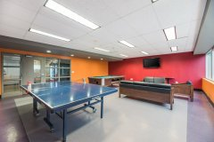 Image of the games room at RCC - Hamilton. There\'s a table tennis table, pool table, TV on the wall as well as a seating area.