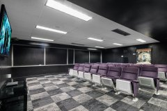 Image of the movie-lounge at RCC - Hamilton. There\'s a large TV on the wall, and cinema style seating.