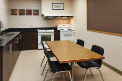 Image of the shared kitchen at RCC - Hamilton. There's two stoves and a table with four chairs.