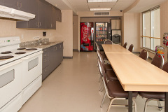 Image of the shared kitchen at RCC-Kamloops. There's two stoves and a table with four chairs.