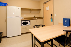 Image of the kitchenette at RCC-Kamloops. There's a full-size fridge, microwave, counter space with sink, and kitchen table with two chairs.