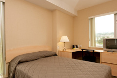 Image of one of the bedrooms in the suites at RCC-Kamloops. Includes a double XL bed, a dresser, desk, chair and Television