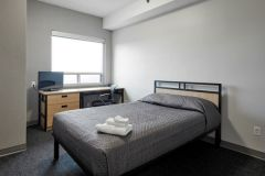 Image of one of the bedrooms in the suites at RCC-King City. Includes a double XL bed, a dresser, desk, chair and Television.
