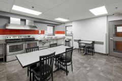 Image of the shared kitchen at RCC-King City. There's two stoves and a table with four chairs.