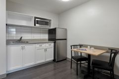 Image of the kitchenette at RCC-King City. There's a full-size fridge, microwave, counter space with sink, and kitchen table with two chairs.