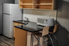 Image of the kitchenette at RCC-Kitchener-Waterloo. There's a full-size fridge, microwave, counter space with sink, and kitchen table with two chairs.