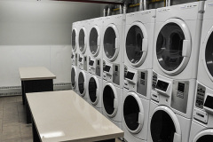 Image of the laundry facilities at RCC-Kitchener-Waterloo. There\'s a number of washing machines and dryers