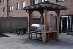 Image of the Back Patio space at RCC-Kitchener-Waterloo. There\'s a number of tables and chairs with umbrellas