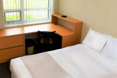 Image of one of the bedrooms in the suites at RCC-London. Includes a double XL bed, a dresser, desk, chair and Television.