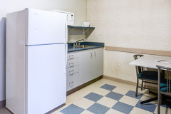 Image of the kitchenette at RCC-Niagara-on-the-Lake. There's a full-size fridge, microwave, counter space with sink, and kitchen table with two chairs.