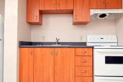 Image of the kitchenette at RCC-North Bay. There's a stove,  full-size fridge, microwave, counter space with sink, and kitchen table with two chairs.