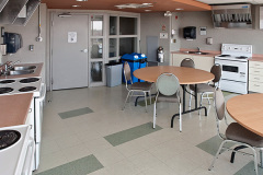 Image of the shared kitchen at RCC-Oshawa. There is stove's and a table with chairs.