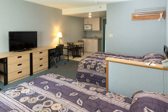 Image of one of the traditional hotel suites at RCC-Oshawa. Includes a 2 double XL bed, a dresser, desk, chair and Television.