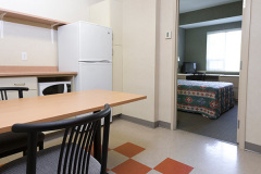 Image of the kitchenette at RCC-Oshawa. There's a full-size fridge, microwave, counter space with sink, and kitchen table with two chairs.