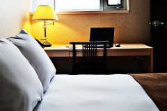 Image of one of the bedrooms in the suites at RCC-Ottawa Downtown. Includes a double XL bed, a dresser, desk and chair.
