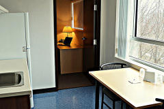 Image of the kitchenette at RCC-Ottawa Downtown. There's a full-size fridge, microwave, counter space with sink, and kitchen table with two chairs.