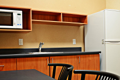 Image of the kitchenette at RCC-Ottawa West. There's a full-size fridge, microwave, counter space with sink, and kitchen table with two chairs.