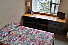 Image of one of the bedrooms in the suites at RCC-Ottawa West. Includes a double XL bed, a dresser, desk, chair and Television.