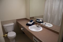 Image of the washroom at RCC-Sarnia. Includes a bathtub with shower, vanity and toilet.