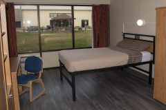 Image of one of the bedrooms in the suites at RCC-Sarnia. Includes a double xl bed, desk and chair.