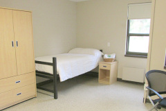 Image of a single bedroom at RCC-Thunder Bay. Includes a single bed, bedside table, desk, chair, microwave and mini fridge.