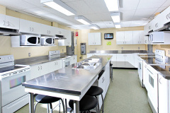 Image of the shared kitchen at RCC-Sudbury West. There's four stoves and sinks with counter space.