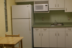Image of the kitchenette at RCC-Sudbury West. There's a full-size fridge, microwave, counter space with sink, and kitchen table with two chairs.