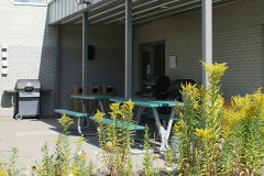 Image of the Back Patio space at RCC-Sudbury West. There's a number of tables and chairs with umbrellas
