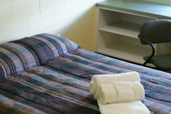 Image of one of the bedrooms in the suites at RCC-Sudbury West. Includes a double XL bed, desk, chair and towels.