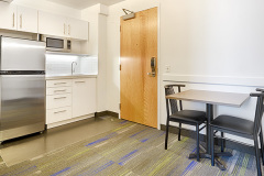 Image of the kitchenette at RCC-Toronto Downtown. There's a full-size fridge, microwave, counter space with sink, and kitchen table with two chairs.