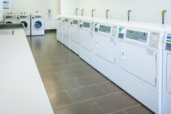 Image of the laundry facilities at RCC-Toronto Downtown. There's a number of washing machines and dryers.