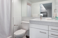Image of the washroom at RCC-Toronto Downtown. Includes a stand-up shower, vanity and toilet.