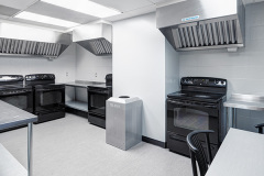Image of the shared kitchen at RCC - Toronto. There's four stoves and a table with four chairs.