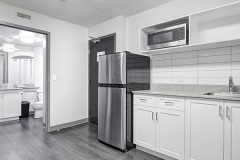 Image of the kitchenette at RCC - Toronto. There's a full-size fridge, microwave, counter space with sink, and kitchen table with two chairs.