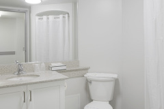Image of the washroom at RCC - Toronto. Includes a stand-up shower, vanity and toilet