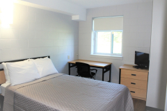 Image of one of the bedrooms in the suites at RCC-Welland. Includes a double XL bed, a dresser, desk, chair and Television.