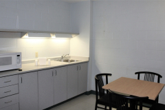 Image of the kitchenette at RCC-Welland. There's a microwave, counter space with sink, and kitchen table with two chairs.