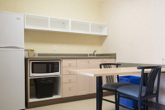 Image of the kitchenette at RCC-Windsor. There's a full-size fridge, microwave, counter space with sink, and kitchen table with two chairs.