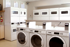 Image of the laundry facilities at RCC-Windsor. There's a number of washing machines and dryers.