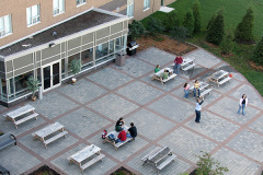 Image of the Back Patio space at RCC-Windsor. There's a number of tables and chairs with umbrellas.