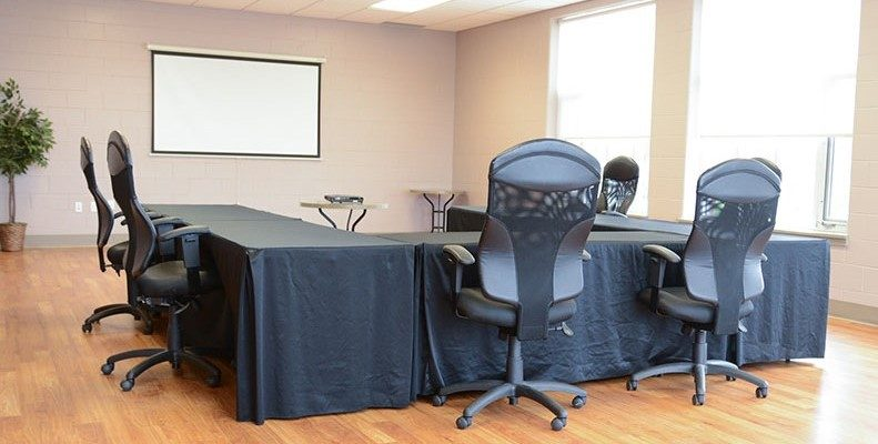 Meeting room set-up in a u-shape. There's a screen, a projector and seating.