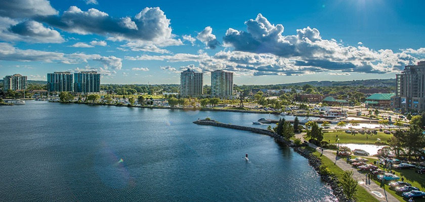 Aerial image of Kempenfelt Bay in Barrie Ontario. There are apartments in the distance and a stand-up paddleboarder is on the lake.