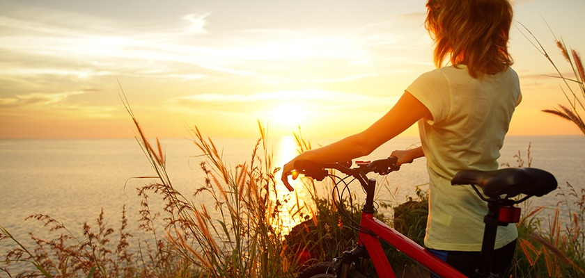 Cycling along the water - someone is standing next to their bike watching the sunset over a lake.