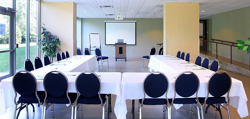 U-shaped meeting room set-up at RCC - Brampton. There is a dais, projector and screen in the background.